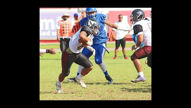 Andrew Toilolo trying to find an open gap between the trenches during the first half of their varsity play-off game against the Sharks last Saturday morning– Tafuna defeated Samoana 14 - 6. [photo: TG]