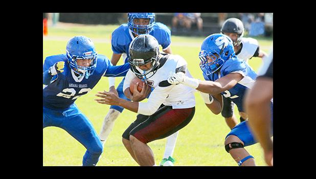 Tafuna Warriors Puletu Fono bracing for impact as he is moments away from being 'sandwiched' by two Shark defenders in the first half of their varsity play-off game. Fono recorded two touchdown catches as he led the Warriors to a 14 - 6 victory. [photo: TG]