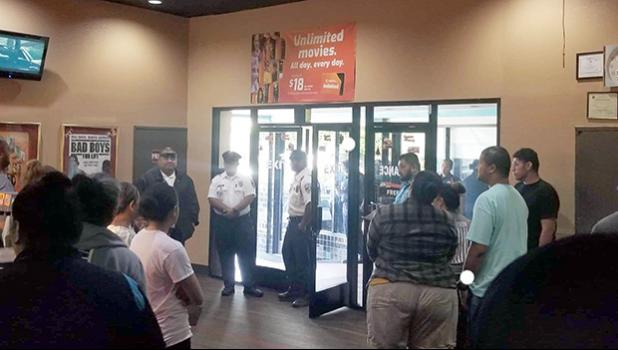 Police standing by the front door as movie goers file out of the Theatre