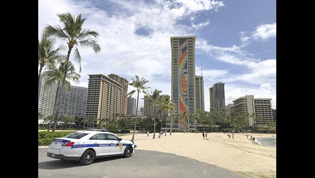 a police officer arrives to tell people to leave Waikiki Beach