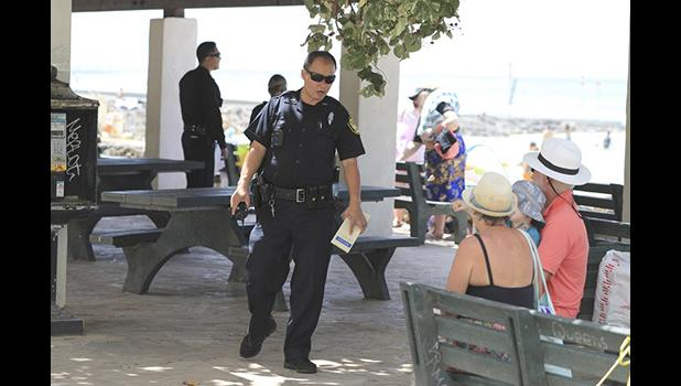 Honolulu police officer telling a couple the beach is closed.
