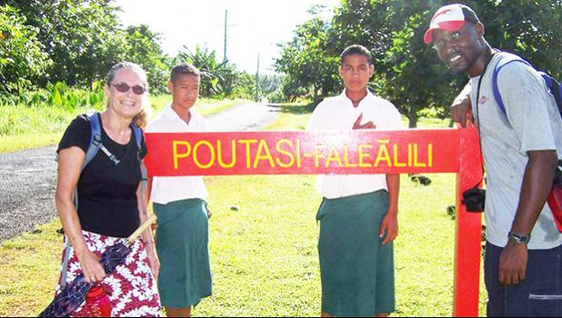 Peace Corps volunteers infron of Poutasi Village sign