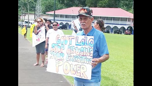 "Pago Pago High Chief Pulu Ae Ae Jr. holds up a sign that reads: ""Gov. Lolo: Stop abusing your executive power"""