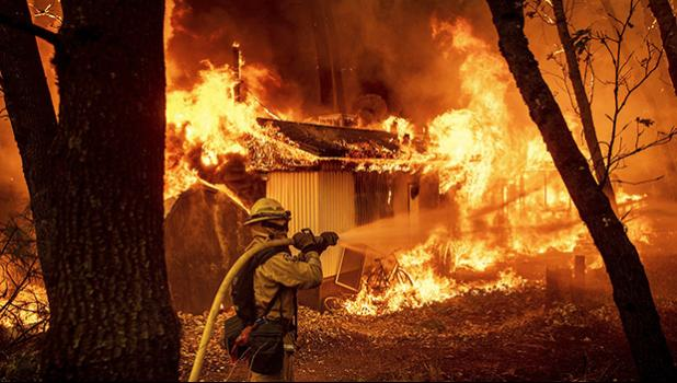 Flames consume a home in Magalia, California, Friday.