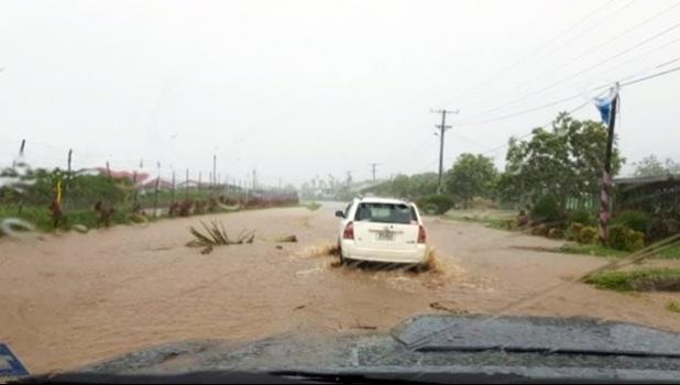 The flooded road at Satapuala, Samoa with cars attempting to drive through
