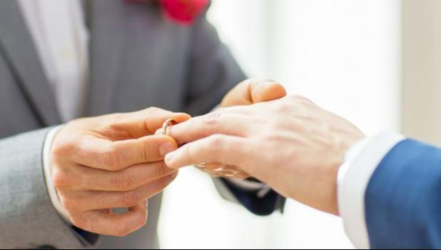 Hands of two men exchanging rings