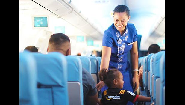 Samoa Airways flight attendant talking with a child on the airplace while another passenger looks on.