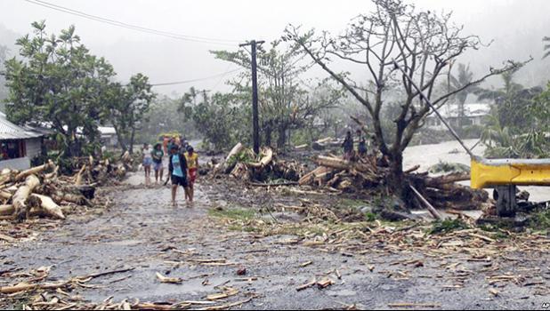 People walk through debris in Samoa's capital Apia, Dec. 14, 2012, after cyclone Evan