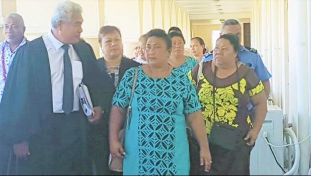 Leutogi Te'o (C) and Luse Tauvale (R) talking to their lawyer