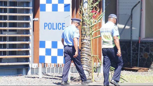 Two policemen outside Samoa's police station