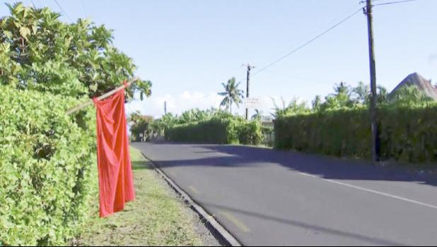 Empty street in Apia with red flag outside a yard.