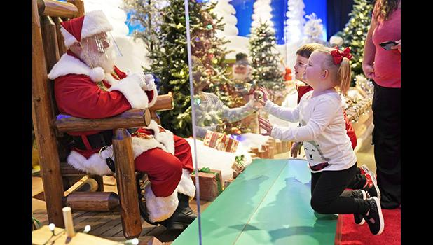 Julianna, 3, and Dylan, 5, visit with Santa through a transparent barrier