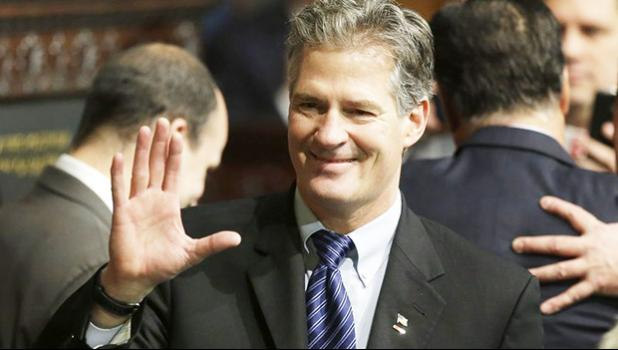 In this Jan. 8, 2015 file photo, former Massachusetts Sen. Scott Brown greets people on the floor of the House Chamber at the Statehouse in Boston. U.S. Ambassador to New Zealand Brown told a New Zealand website Wednesday, Oct. 25, 2017, he accepted advice that he should be more culturally aware after a U.S. inquiry into his conduct at a Peace Corps event in Samoa. The Stuff news outlet says Brown acknowledged complaints were made about his comments to a female food server at the event and to guests upon hi