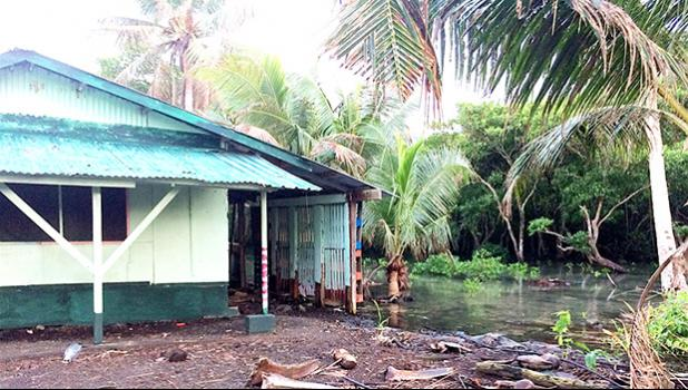 The tide can be seen coming dangerously close to a home in Nuuuli,