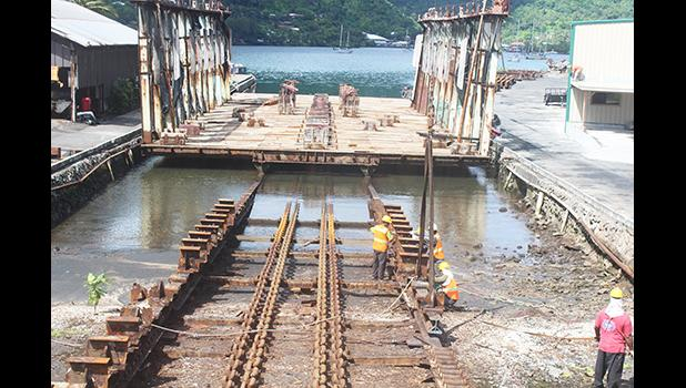 Ronald Reagan Shipyard employees working on repairs to the front portion of the 3,000-ton slipway at Satala yesterday morning.