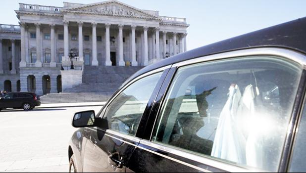 Extra shirts hang inside of a senator's vehicle as the Capitol dome is reflected on Capitol Hill as a bitterly-divided Congress hurtles toward a government shutdown this weekend, Friday, Jan. 19, 2018, in Washington. (AP Photo/Jacquelyn Martin)