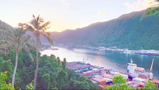 Sun just behind the mountains as it rises over Pago Pago bay