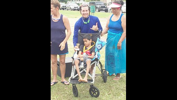 Athlete Miracle Singh, a 10-year-old from Leone poses with a volunteer, Earl, and his family after receiving a trophy and silver medal during the awards ceremony after the adaptive aquatic Swim Meet held last Saturday in Utulei.  [Photo: Ese Malala]