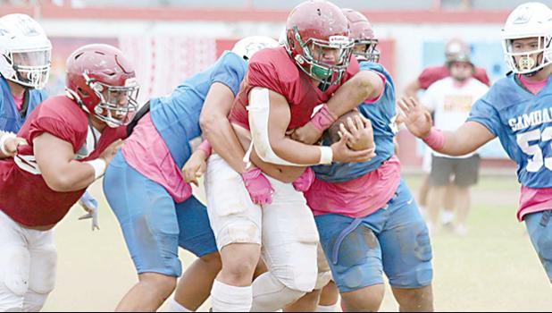 Tafuna High School's powerback is gang-tackled by three Samoana defenders