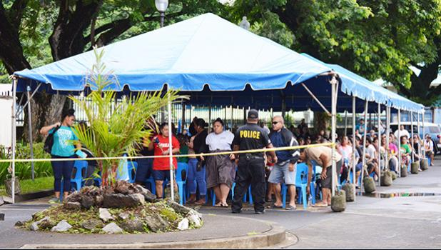 Large crowd under tents in the parking lot of the Territorial Bank of American Samoa