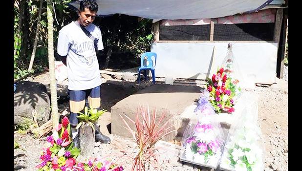 Tu'ivale Luamanuvae beside the graves of his three children