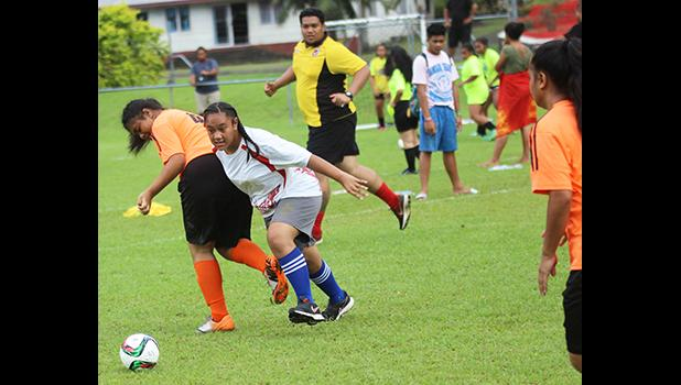 A Vaiala Tongan player dribbles by an Utulei Youth defender