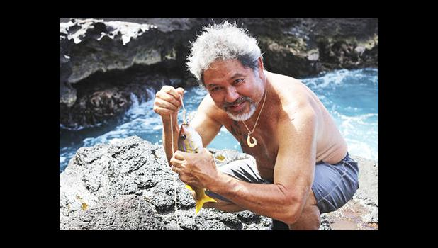 In this July 4, 2015, file photo provided by the Office of Hawaiian Affairs, G. Umi Kai uses a traditional Hawaiian hook to catch a fish at the Papahanaumokuakea Marine National Monument in Hawaii. Kai supports a plan to expand the monument. The White House says that President Barack Obama will expand the national monument off the coast of Hawaii, creating the world's largest marine protected area.  [Keola Lindsey/Office of Hawaiian Affairs via AP]