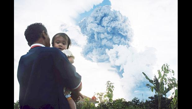 In this Sunday, June 9, 2019, file photo, a man carrying a child watches Mount Sinabung spew volcanic material into