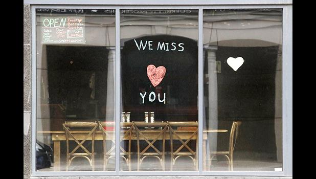 """Sign in the window of empty cafe saying, """"We miss you"""""""