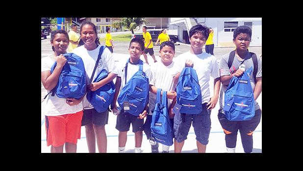 Meet the junior division champions of the first annual Manumalo Church Basketball Fellowship League: the white team, led by player coach Fitzgerald Alofa (3rd from right). The players received backpacks and school supplies provided by Papalii Laulii Alofa, who was also the head coach for the white team. See story for full details. [Courtesy photo]
