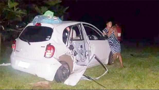 Person leans against front of wrecked white car