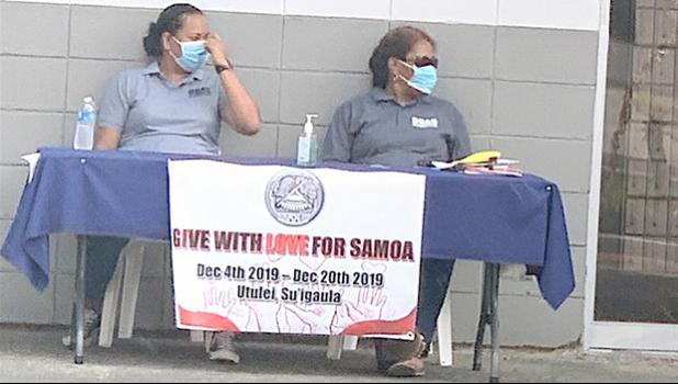 Two ASG workers wearing protective nose/ mouth masks,
