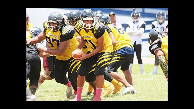 Daniel Fano of Nu'uuli, looking to send one of his backers on a running play, in the opening half of their Varsity match against the Warriors.  [photo: TG]