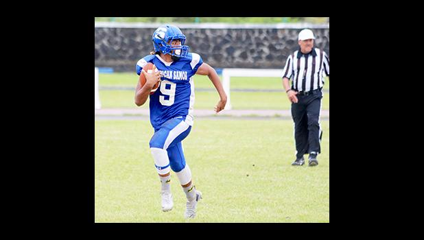 Samoana quarterback Anthony Feala, storming through mid-field as he checks for nearby defenders – in the second half of their JV game last Saturday morning. Feala led the Sharks in their 18 - 0 win against Nu'uuli, as their final game of the season.  [photo: TG]