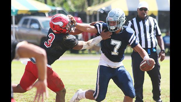 Samoana Sharks quarterback Viliamu Tanielu trying to hold off a vicious blitz by Ronnie Oa of