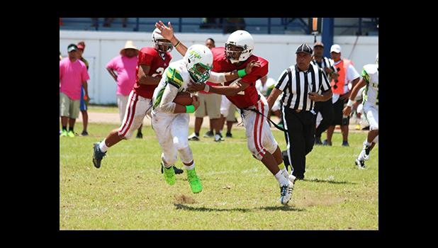 Leone Lions quarterback, Iverson Ta'ase trying to evade the Vikings defensive back – a touchdown saving tackle that nearly saw Ta'ase break loose towards the end zone. Faga'itua won the JV game 28 - 14. [photo: TG]