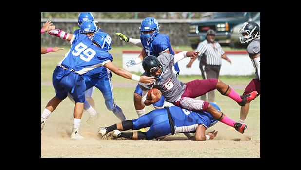 Pete Fa'avae of the Warriors taken down there by Samoana's Cornelius Aiava, in the opening half of their varsity game last Saturday morning. The Warriors defeated the Sharks 28 - 12. [photo: TG]