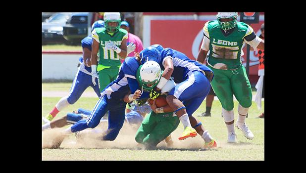 David Mikaele and Vimoto Mageo sandwich tackle Leone Lions running back Luteru Ah Loe, in the opening half of their varsity rivalry game last Saturday – Samoana won over the Lions 6 - 0. [photo: TG]