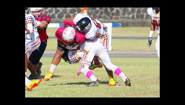 Two Warrior defenders taking down Faga'itua's work horse T.I. Farani during the opening quarter of their Battle of the Toa's varsity rival game last Saturday morning. Warriors are now No.1 in Varsity competition in ASHSAA Football League competition. [photo: TG]