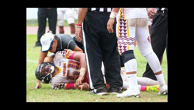 ATC Florence Wasko tending to the injured So'oso'o Letuli, Warriors middle linebacker, as he came down with a shoulder injury, in the second half of their varsity game against the Lions last Saturday – Letuli came back later to help the Warriors in their 20 - 6 win over Leone — keeping their No.1 seed heading into playoffs. [photo: TG]