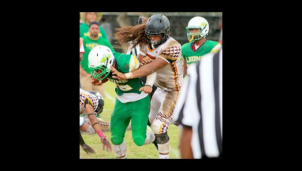 Leone's new quarterback Ui'ese getting hammered by Penei Pavihi as Ui'ese finally gets acquainted with one of Tafuna's finest, in the second half of their varsity game.  [photo: TG]