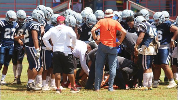 Samoana Sharks varsity squad huddling around one of their injured players