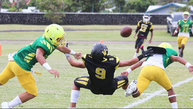 A pass from Jerry Isaako of the Wildcats intended for his wide receiver is broken up by Ben Tikeri