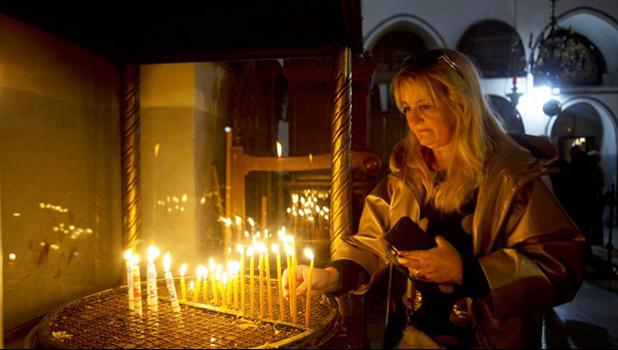 A visitor lights a candle at the Church of the Nativity built