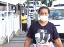 A woman walking on the street in Apia wearing a mask