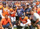 The defensive line group — Derek Wolfe (95), Shelby Harris (96), Zach Kerr (92), Domata Peko Sr. (94), Kyle Peko (90), DeMarcus Walker (57) and Adam Gotsis (99) — take a group photo with Peko Sr.'s father
