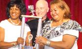 In this photo: (right) President Isapela Coggins is presented the American Samoa Society's National Trophy by last year's winner, (left) Diane Parrot, who represents the Virgin Islands Society, along with (center) NCSS President William Christian.  [Courtesy photo]