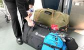 A United Airlines employee checks in two Pacsafe rolling duffels at Vancouver International Airport for Cool Stuff's journey back to the islands, after coverage of the 2018 Canada 7s.  The blue Pacsafe backpack has two pro bodies, lenses, flash, memory cards, batteries and MacBook Pro laptop... all compressed to fit properly in the overhead.  [photo: Barry Markowitz]