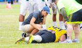 Certified Athletic Trainer (ATC) Florence Wasko (left) tending to one of the injured Nu'uuli Wildcats football players during week two of ASHSAA Football action this season. Every game so far has seen injuries —some season-ending, others from 'old' injuries, while others are concussions. [photo: TG]