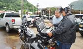 """WELCOME TO THE 21ST CENTURY: Police senior officer, Lomu Mosese (left), demonstrated yesterday for a motorist, the Department of Public Safety's new """"electronic citation"""" or e-Ticket system, in which a police officer uses a laptop to issue a traffic violation ticket to a driver and the citation is automatically transmitted to the District Court. [photo: AF]"""